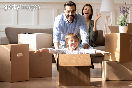 Excited parents with little son having fun on moving day