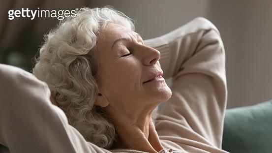 Calm senior woman relax on sofa breathing fresh air