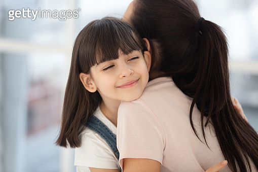 Little girl hugging mom showing love and care