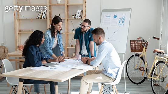 Serious businesswoman mentor speaks in coworking boardroom at meeting.