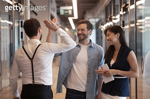 Employees standing in hallway greeting each other giving high five