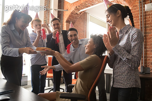 Happy African American businesswoman receiving cake from smiling colleagues