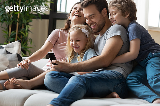 Happy parents with little kids use cellphone at home