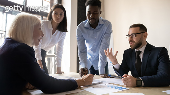 Young and older leaders consider business ideas collaborating at meeting