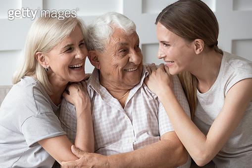 Portrait of happy elderly parents and adult daughter hugging
