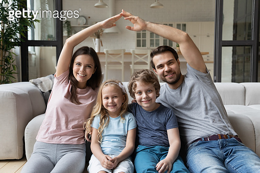 Parents making shape of house roof over head of children