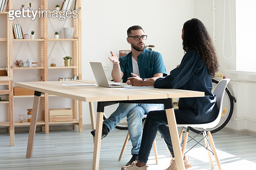 Confident bearded businessman talking with businesswoman using laptop in boardroom.