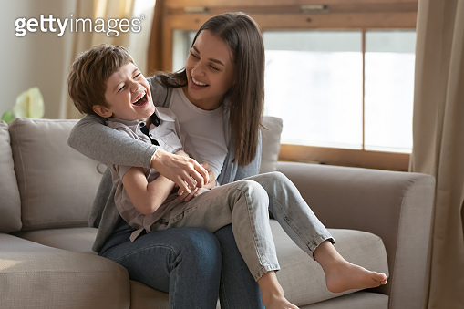Happy young mommy tickling laughing small child son.