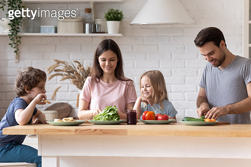 Smiling young family cooking together in kitchen