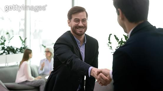 Happy businessman in eyeglasses shaking hands with partner.