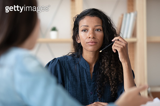 Close up focused african american businesswoman listening new female applicant.