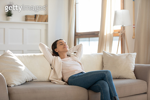 Relaxed young woman rets on sofa enjoying weekend
