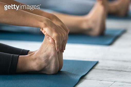 Closeup focus on woman feet and arms during Paschimottanasana pose
