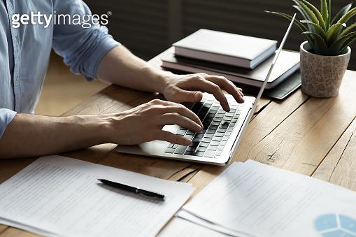 Close up businessman using laptop, sitting at work desk