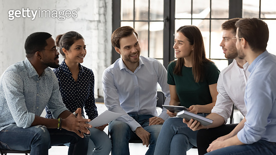 Smiling multiracial colleagues engaged in teambuilding in office