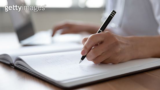 Female doctor hand making notes in journal using laptop
