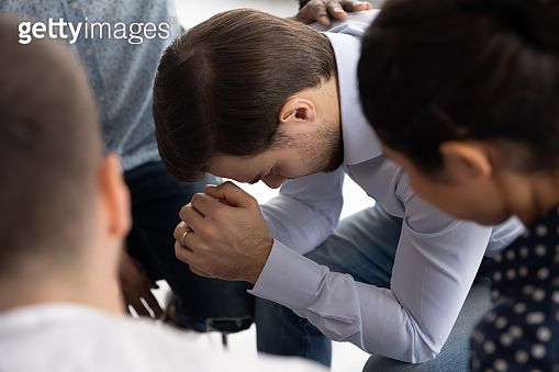 Diverse patients comfort depressed man at group therapy
