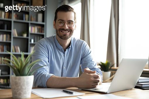 Head shot portrait smiling businessman wearing glasses sitting at desk