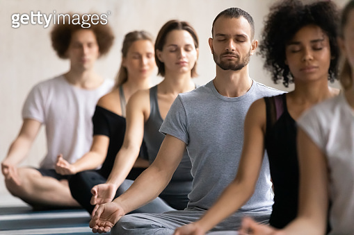 Group of diverse people meditating visualizing during yoga session