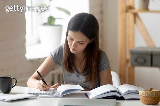 Concentrated female student handwrite studying at home