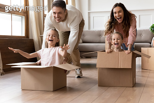 Laughing family couple having fun together with adorable daughters.