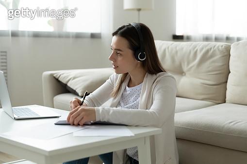 Focused woman in headphones watch webinar on laptop writing notes