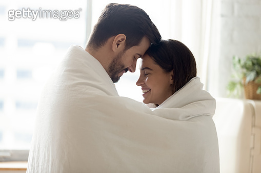 Happy loving couple wrapped in warm blanket touching foreheads