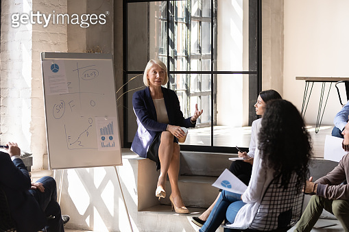 Middle-aged woman business trainer teaches group of young specialists