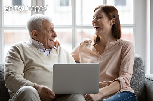Overjoyed old 70s retired father watching funny movie with daughter.