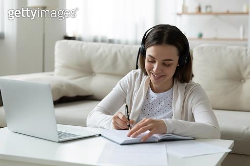Smiling woman wear headset watch webinar writing notes