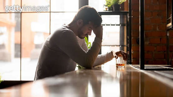 Depressed upset man drinker addicted to alcohol drink whiskey alone