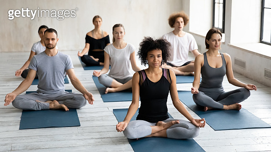 Diverse young people seated cross-legged practicing meditation together indoors