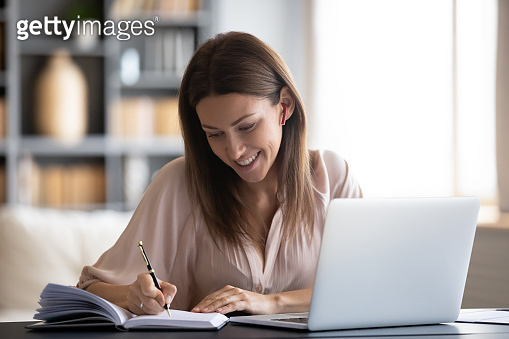 Smiling woman writing in notebook, using laptop at home