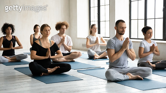 Seven diverse people folded hands Namaste symbol meditating indoors