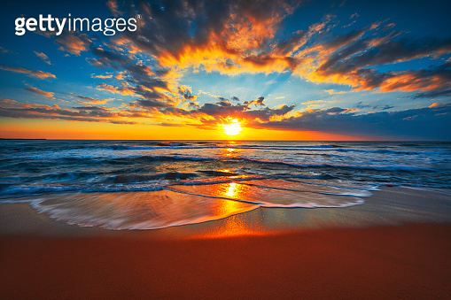 Sunrise on the beach and ocean waves on a tropical sea