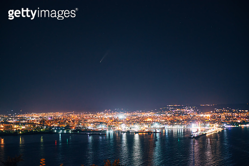 Night view toward Varna, Bulgaria. Seascape with reflection of city lights and neowise in the stars