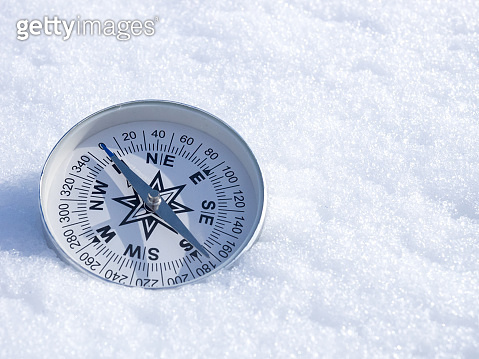 Round modern compass on the white snow, space for text. Concept for travelling and active lifestyle