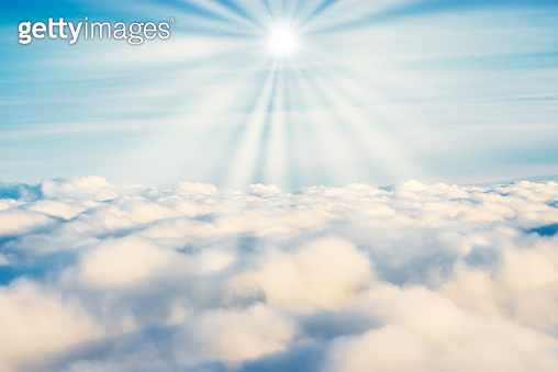 White clouds on blue sky with sun rays