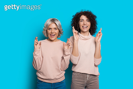 Dreamy ladies with curly hair are posing with opened mouth on a blue wall with crossed fingers showing their tongues