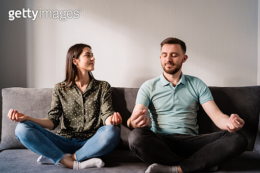 Man and woman sitting on sofa in lotus pose