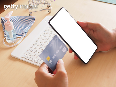 Woman holding smartphone with a blank screen and credit card mockup at office desk, concept financial transaction.
