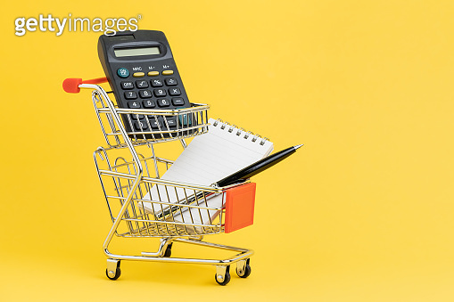 Shopping list, check out and payment or shopping calculation concept, calculator, notepad and pen for writing list in miniature double baskets shopping cart or shop trolley on yellow background