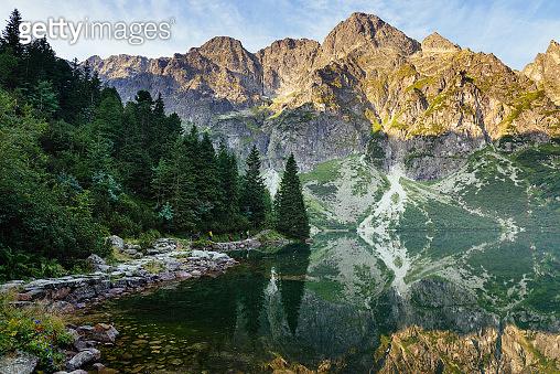 Amazing landscape with high rocks and illuminated peaks, stones in mountain lake(Morskie Oko), reflection at morning sunrise. Concept awakening and harmony with nature. Tatra National Park. Europe.