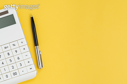 Flat lay or top view of black pen with white calculator on vivid yellow background table with blank copy space, cost and expense, budget, tax, math or investment calculation