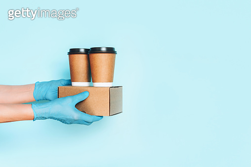 Hand in medical gloves carrying paper coffee cup coffee, lunch box on blue background. Banner, copy space. Contactless delivery service during quarantine coronavirus pandemic. Take away only concept