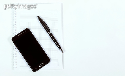 Smartphone, pen and notebook on a white background close-up, business concept
