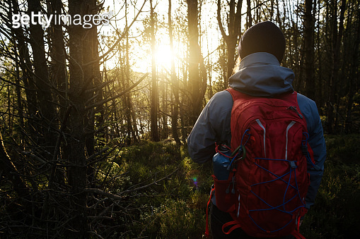 Woman outdoor adventures: hiking in Norway at sunset