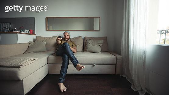 Life during covid-19 pandemic lockdown: man in quarantine at home watching TV