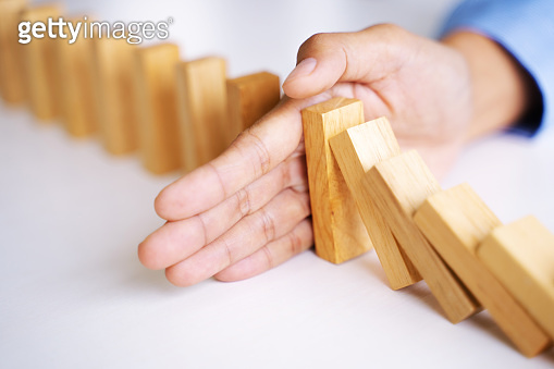 Female hand stopping wooden brick block,  risk and security solution concept.