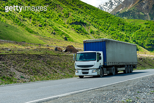 Wagon transports cargo on a mountain road in a picturesque place in the Caucasus